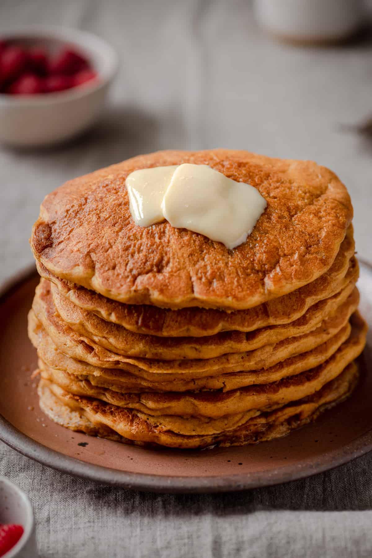 softened vegan butter sitting on a stack of vegan pumpkin pancakes