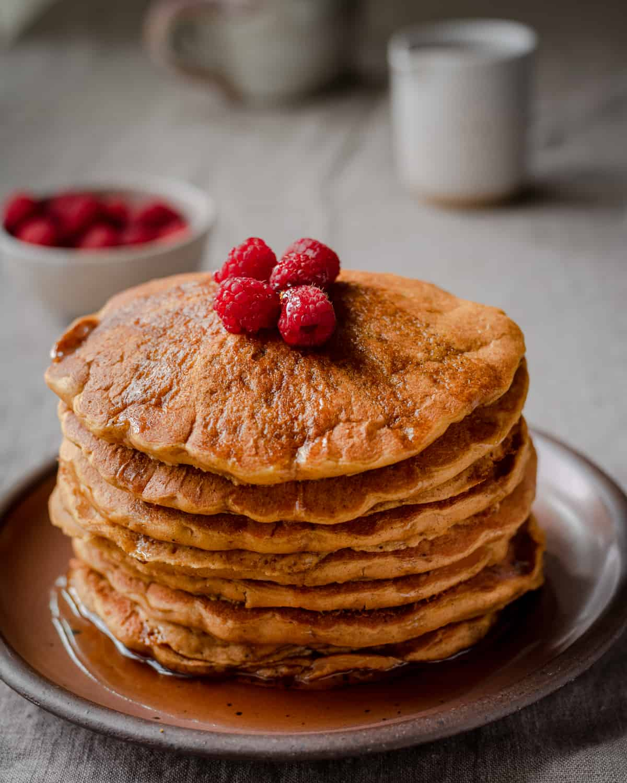 a stack of vegan pumpkin pancakes with raspberries on top